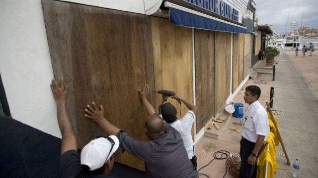 Vecinos de protegen sus viviendas ante la llegada del huracán.