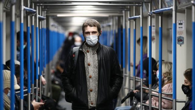 Homem com uma máscara dentro de um vagão do metrô de Moscou