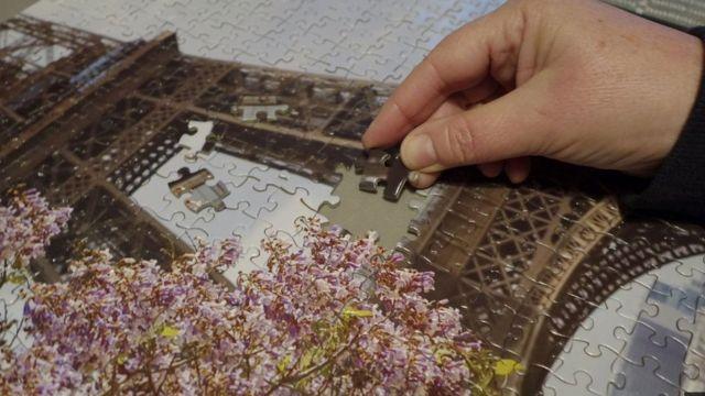 Close em uma mão terminando de montar um quebra-cabeça da Torre Eiffel