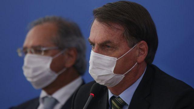 Sentados e de perfil, Paulo Guedes e Jair Bolsonaro de máscara