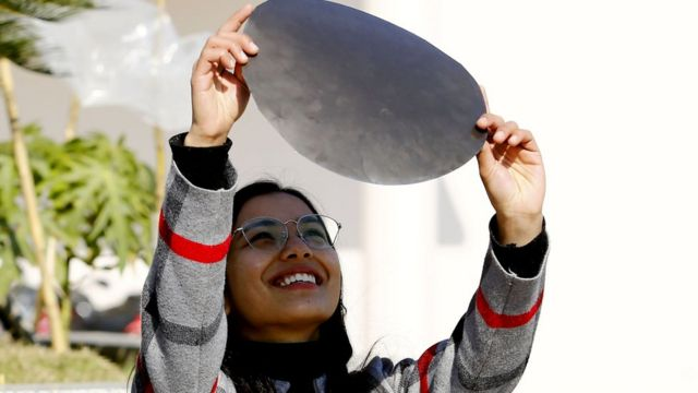 काठमाण्डूबाट सूर्य ग्रहण हेर्दै एक महिला