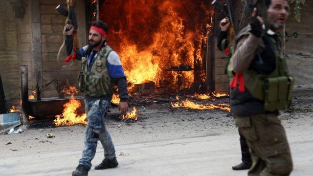 солдаты на фоне горящего магазина в Африне