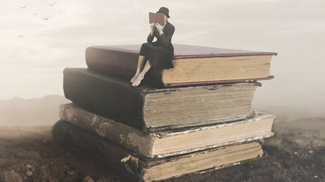 Surreal image of a woman reading, sitting on top of a pile of books