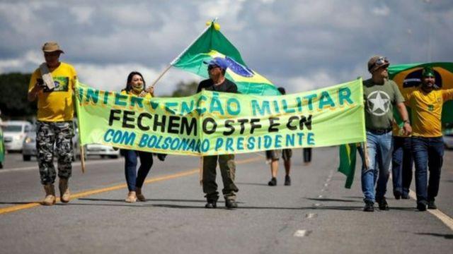 Manifestantes seguram cartazes pedindo fechamento do STF e do Congresso durante ato pró-Bolsonaro