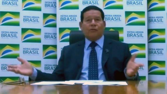 Em transmissão online de vídeo, Mourão aparece sentado diante de mesa, gesticulando com braços abertos enquanto dá entrevista, com painel escrito 'Pátria amada Brasil' atrás