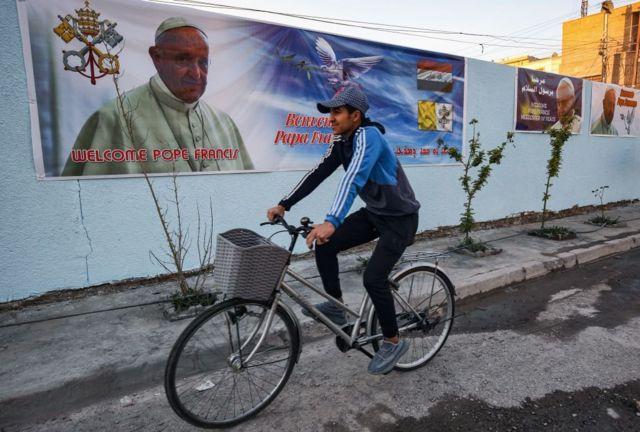 ملصقات احتفالية بزيارة البابا في أحد شوارع بغداد