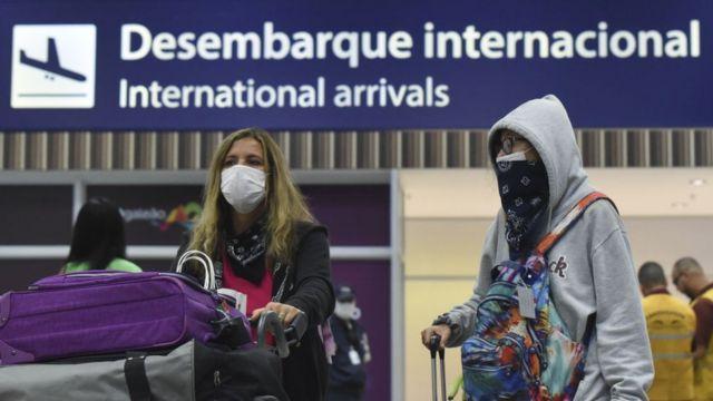 Dos personas con mascarillas en un aeropuerto de Brasil.