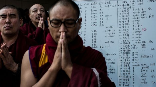 Monks pray near a collapsed building on February 7, 2016 in Tainan, Taiwan