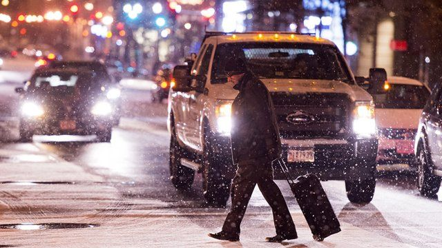 Man crosses the road in front of traffic with snow falling