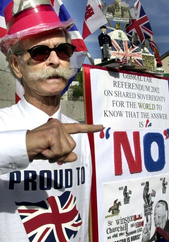 """Un manifestante con una camisa que dice """"Orgulloso de"""" y una bandera británica"""