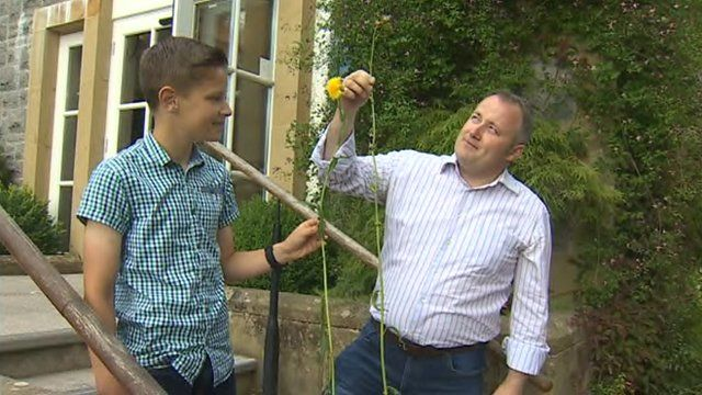 Darren Millar and son Toby with giant dandelion