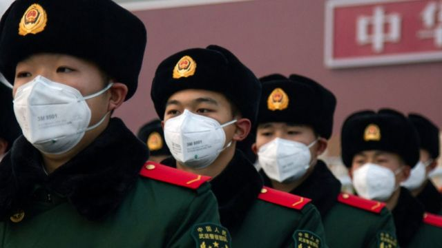 Soldados chinos con mascarillas en frente de Tiananmen.
