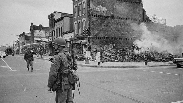 Un soldado frente a un edificio destruido