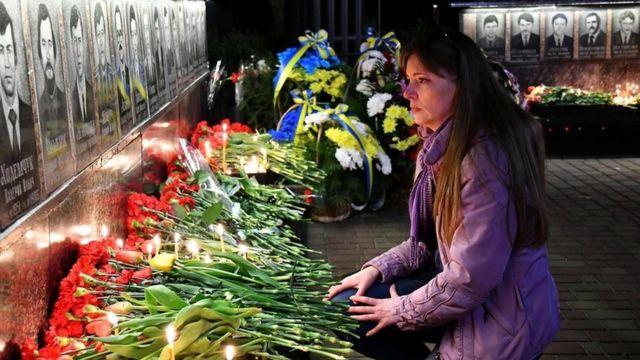 Una mujer deja flores frente a un homenaje a las víctimas de Chernóbil.