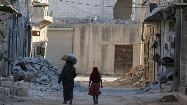 Una mujer y una niña caminan por las calles destruidas de Alepo.