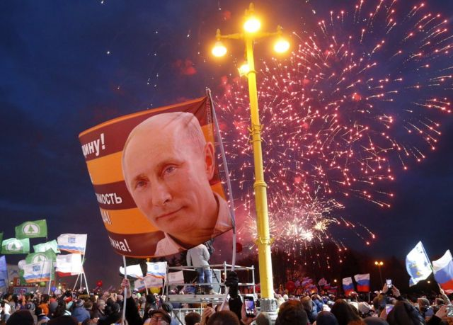 Люди держат нациоональные флаги и портреты с изображением Владимира Путина