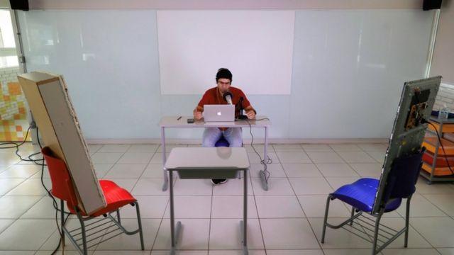 O professor Fabiano da Silva em sala vazia, em frente a laptop e falando no microfone para alunos