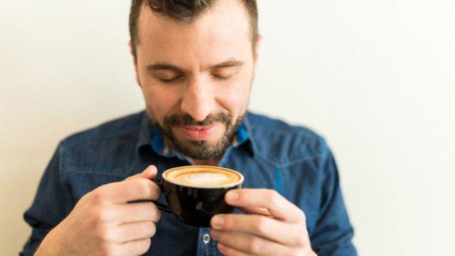 Hombre joven con los ojos cerrados inhala el aroma de una taza de café en sus manos