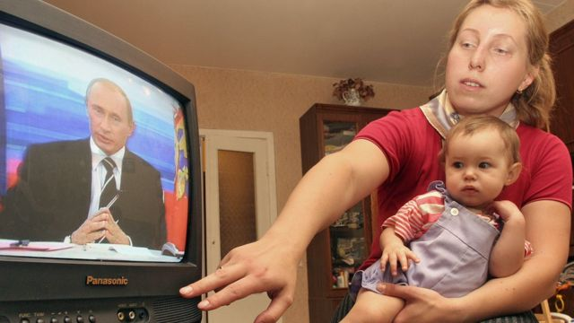 Женщина с ребенком смотрят телевизор