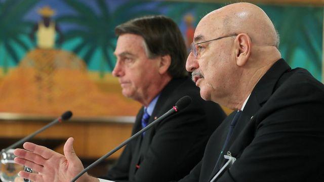 Osmar Terra fala ao microfone, com Jair Bolsonaro no plano de fundo. Ambos estão sentados diante de mesa em sala