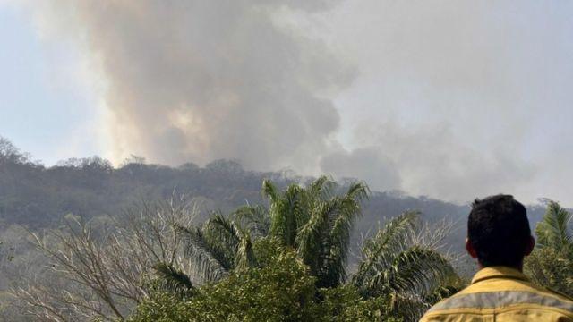 Un hombre mira el humo de un incendio en Bolivia.