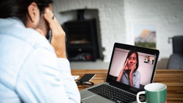 Un hombre conversa con una mujer a través de una videollamada por computador.