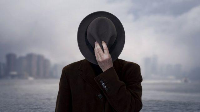 Мужчина прикрывает лицо шляпой