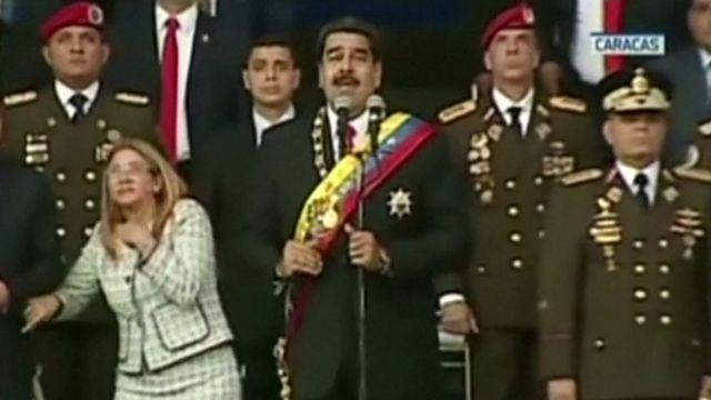 国家警備隊の創立記念式典中に起きた大きな爆発音に反応するニコラス・マドゥロ大統領(中央)と大統領夫人のシリア・フロレス氏(左)