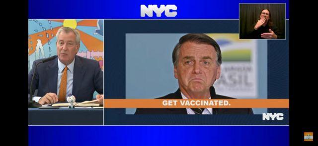 Bill de Blasio em programa de TV nos EUA ao lado de foto pedindo para que Bolsonaro se vacine