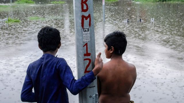 Dos menores observan una zona inundada