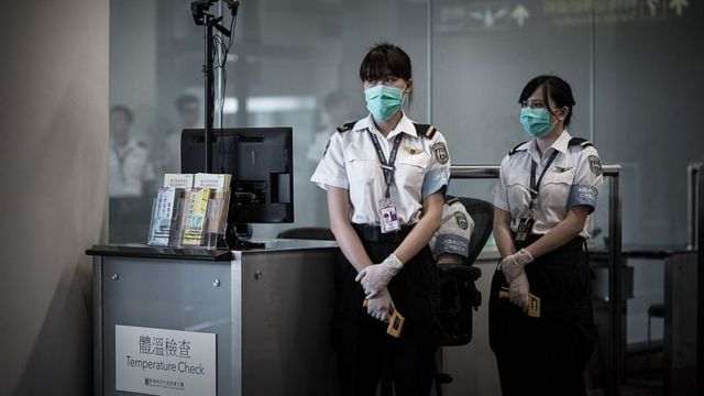 Airport personnel wait for passengers to check their temperature as part of preventive measures against the spread of Middle East Respiratory Syndrome (MERS) at the Hong Kong international airport on June 5, 2015.