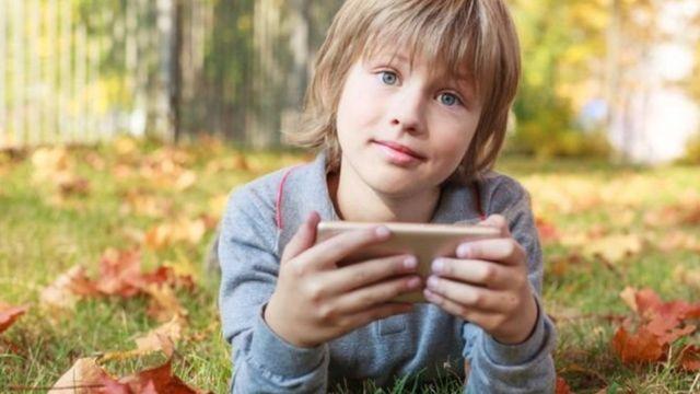 طفل يستخدم هاتف محمول