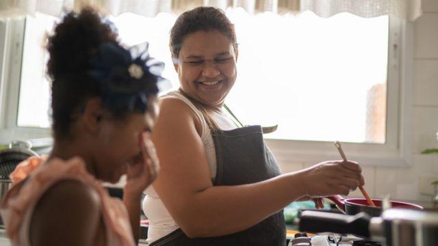 Mulher cozinha e conversa com criança, sorrindo