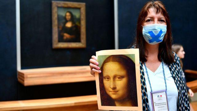 Mulher segurando um cartaz da Mona Lisa em frente ao quadro no Museu do Louvre