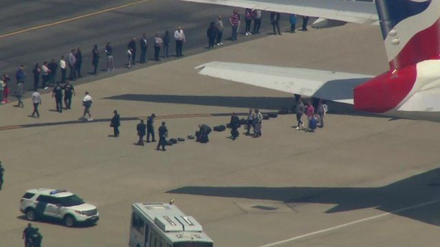 Shows passengers coming out of parked plane and putting their suitcases on the tarmac