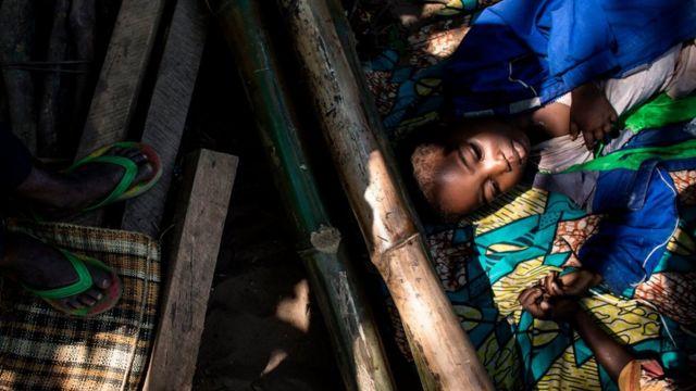Un niño descansa junto a otras personas desplazadas mientras esperan por su ración diaria de comida en un cnetro para desplazados en Kikwit, en la provincia de Kasai.