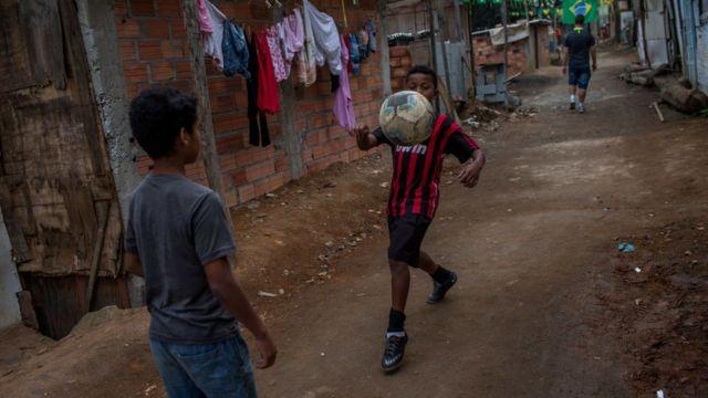 Niños jugando con una pelota de fútbol en una favela.