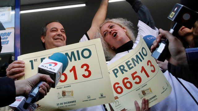 Owners of a lottery shop celebrate after selling the lottery ticket 66.513 winner of the jackpot of El Gordo lottery in Madrid