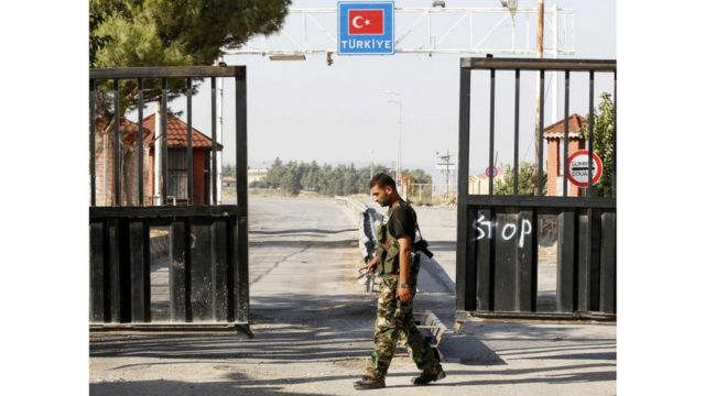 أحد عناصر الجيش السوري الحر يحرس باب السلام على الحدود السورية التركية في عام 2012
