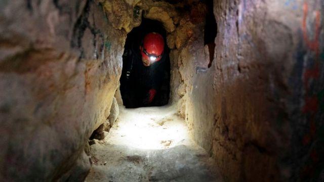 Hombre atravesando un túnel en las catacumbas de París.