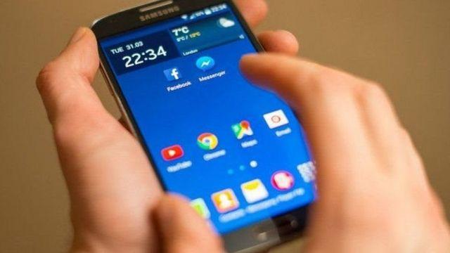 હાથમાં મોબાઈલ ફોન રાખીને મોબાઈલ ફોનની સ્ક્રીન તરફ જોઈ રહેલા મોબાઈલ ફોન ધારકની પ્રતિકાત્મક તસ્વીર