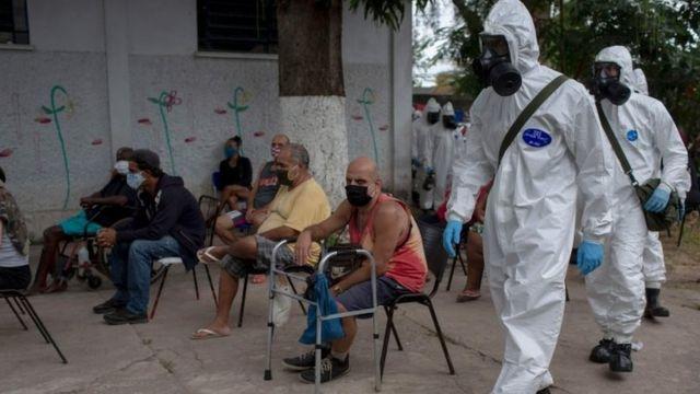 Soldados brasileños en trajes protectores se preparan para desinfectar un albergue público en Río de Janerio
