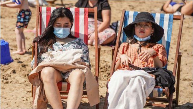 Pessoas na praia usando máscaras