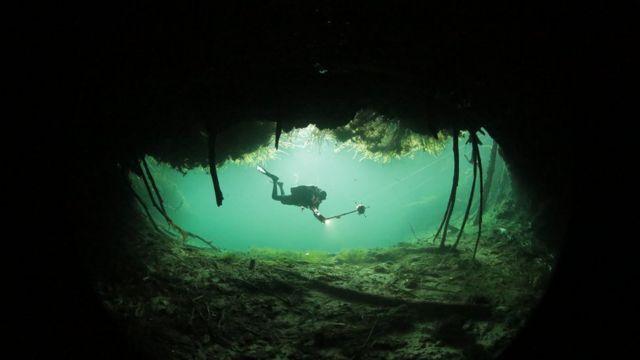 Buzo nadando en una cueva