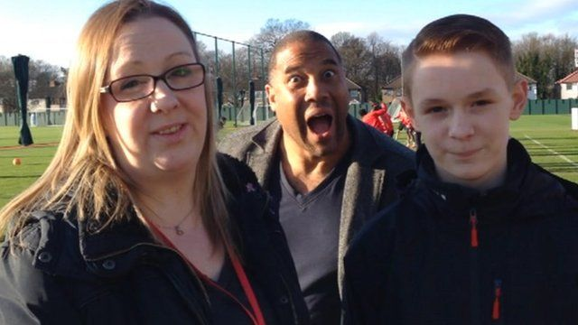 Liam and Charlotte Hennessy being photobombed by John Barnes