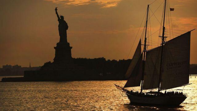 Vista de la estatua de la libertad al atardecer, con un barco antiguo de vela en la bahía