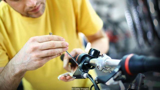 Homem faz ajuste em bicicleta