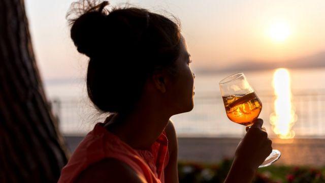 Una chica toma un spritz frente a la playa