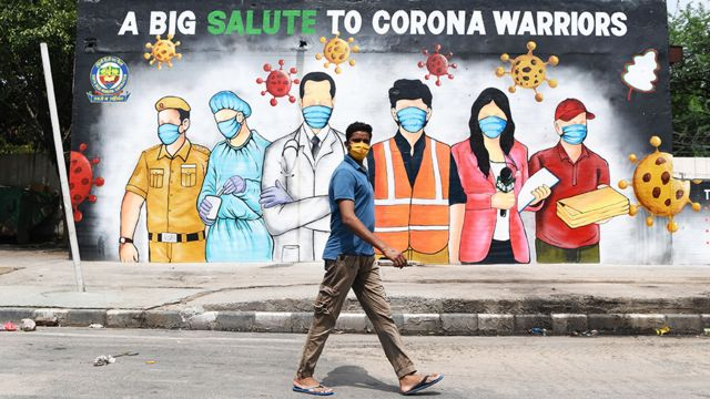 A man wearing a facemask walks past a Covid-19 mural in New Delhi , India - 31 May 2020