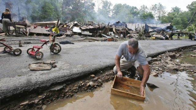 A man cleans out a box with creek water as he cleans up from severe flooding in White Sulphur Springs, West Virginia.